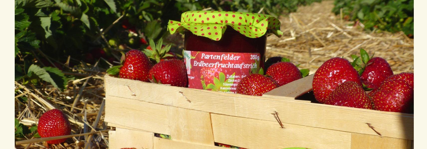 gefüllter Erdbeerkorb zusammen mit einem Glas Partenfelder Erdbeerfruchtaufstrich